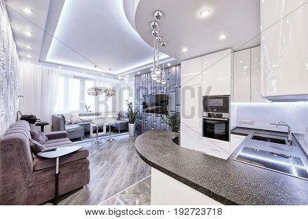 Modern design interior room with white gloss kitchen in a luxury apartment in gray and white tones.