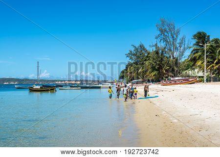 Ramena Madagascar - December 20 2015: Unidentified Malagasy children and teenagers go along the Ramena beach in a fishing village of Ramena Madagascar.