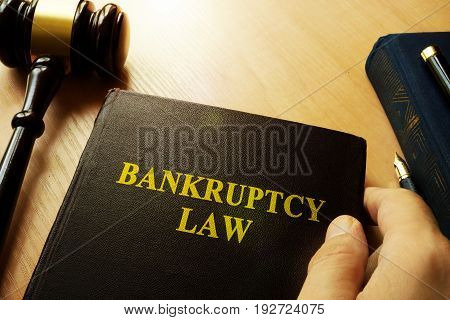 Hands holding Bankruptcy Law in a court.
