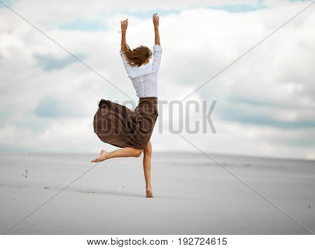 Young woman jumps on sand in desert. She is dressed in long skirt and blouse.