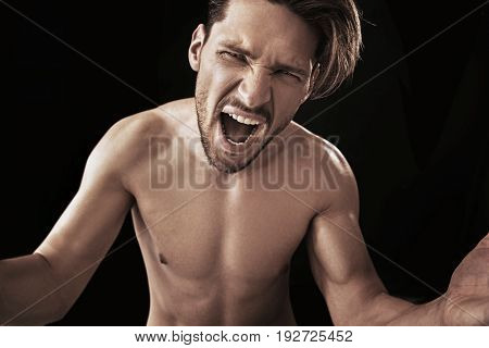 Crazy angry man shouting with mouth wide open gesturing with hands towards the camera