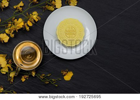 Sweet color of snow skin mooncake and tea cup with flowers on dark background.
