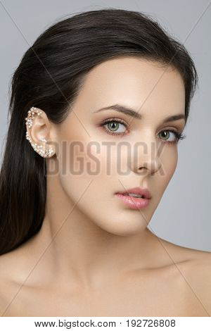 Beautiful young woman with natural make up and pearls glued on ear. Beauty shot on grey background. Copy space.