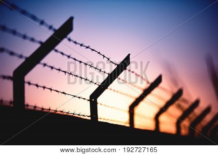 Wall with barbed wire and a sunset in the background.