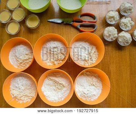 Cookery Set Of Orange And Green Cups With Flour, Sugar, Yeast And Condensed Milk Stand At Light Brow