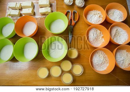 Cookery Set Of Orange And Green Cups With Flour, Sugar, Yeast, Condensed Milk And Blocks Of Butter S