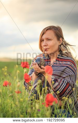 Woman In Poncho With Calabash On Flower Field