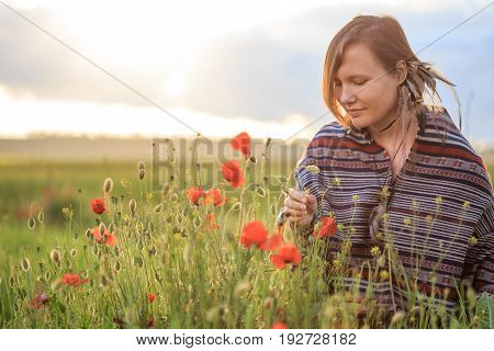 Woman In Poncho Sits On Sunset Flower Field