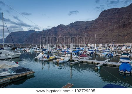 Night view of marina Los Gigantes. Sailing and motor boats, steep rocks and late evening light. Tenerife island, Spain.