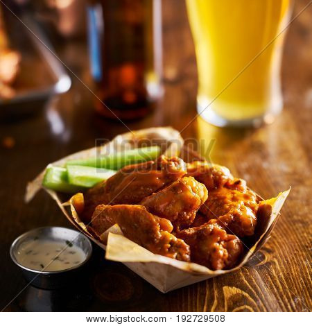 pile of tasty buffalo chicken wings in paper tray with celery and beer