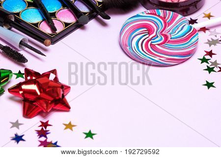 Holiday party make up products with lollipop, confetti and gift wrap bows. Selective focus, copy space