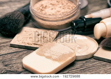 Foundation, concealer, powder with cosmetic sponge and professional makeup brushes. Shallow depth of field, toned image