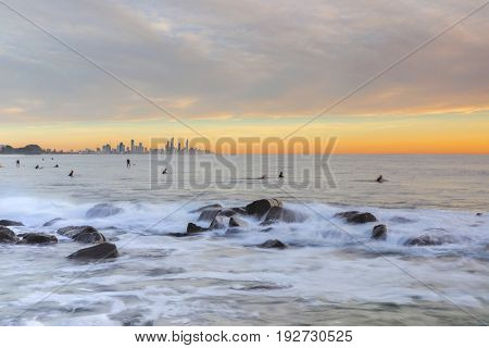 Sunrise lighting up the sky at Burleigh Heads Gold Coast, with ocean rocks and surfers.