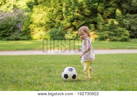 Little child is playing with football ball in park.