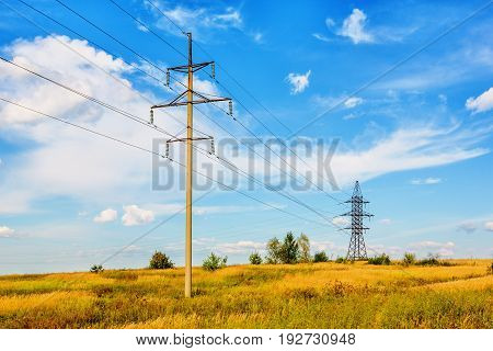 High voltage line beneath blue cloudy sky