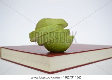 A cut green apple on a red book