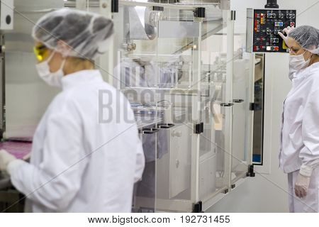 Pharmaceutical Production Line Workers. An employee oversees the packaging of the medical pills.