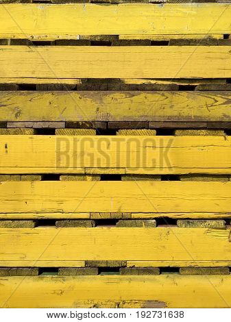 Closeup of several yellow wooden pallets for transportation