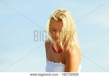 Feminine portrait of beautiful woman wearing white dress clear blue sky in background.