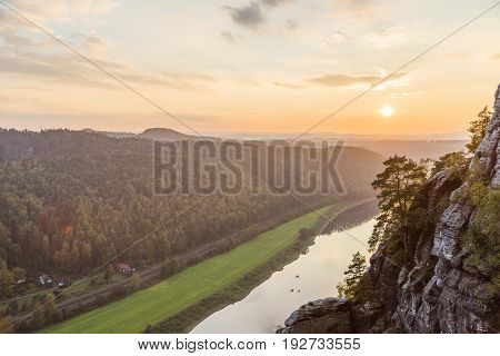 View from a high mountain to a narrow river in the middle of a dense wild forest in a bright sunny summer or autumn day