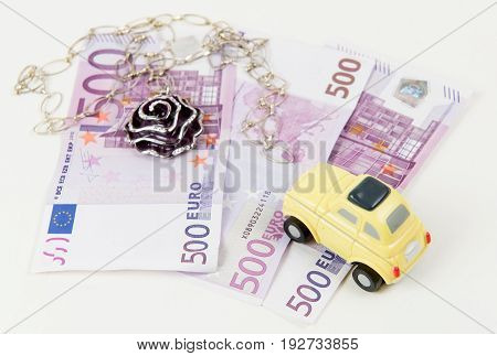 500 Euro bank notes car and jewelry. Concept of consumerism and money spending