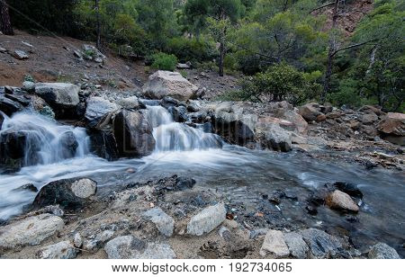 Water flowing in a mountain river creating small waterfalls at Troodos mountains Cyprus