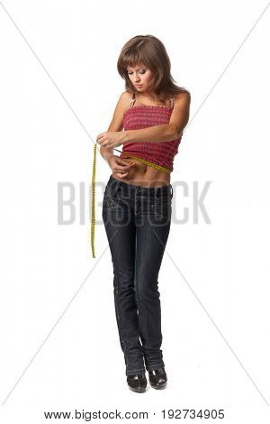 The beautiful girl measures a waist on a white background.  Healthy lifestyles concept.