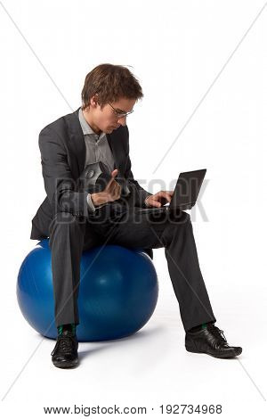 The young businessman simultaneously works on the computer and and does exercise with dumbbells.