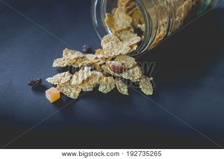 whole grain cereal flakes which mixed berry fruit and raisins. Cereal cornflake for breakfast on black background