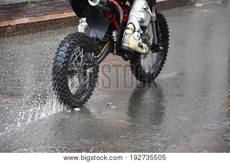 The motorcycle rides on the water with a spray