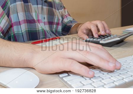 The Man and computer are using a calculator on the table in the office room. accounting and business concept. The Man sits at the table with a computer and business accessories
