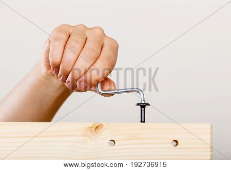 Human hand assembling wooden furniture using hex key. DIY enthusiast. Home improvement.