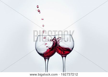 Two wine glasses in toasting gesture with big splashing at studio.