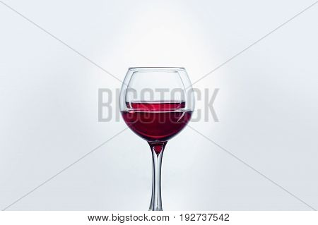 Two wine glasses with red wine against white