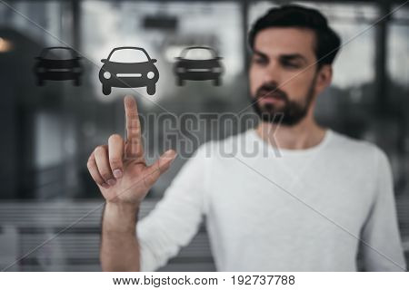 Handsome man is touching virtual screen with car icon.
