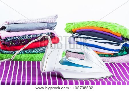 Stack Of Clothing And Iron On A White Background