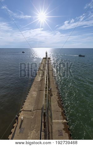 The view toward the setting sun and Lake Michigan is captured from atop the St. Joseph North Pier Inner Lighthouse. The smaller Outer Light is seen at the end of the breakwater.