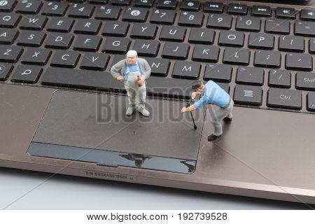Mini Workmen Repairing A Laptop Key Board.