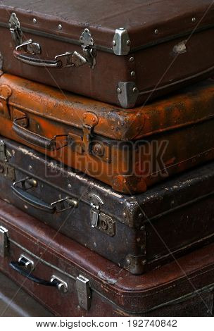Stack of four old vintage antique grunge travel luggage brown leather suitcase trunks close up high angle side view