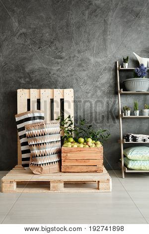 Small pantry with wooden pallets and box with apples in loft