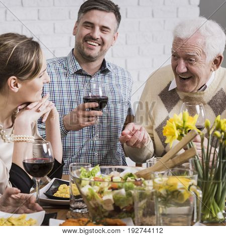 Happy family sitting beside table during dinner smiling