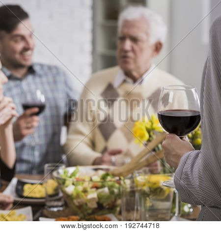 Happy family sitting beside table during sunday meal drinking wine