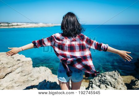 Back View Of Young Woman With Raisied Hands On Top Of Cliff Above Beautiful Sea