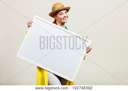 Happy cheerful woman wearing sun hat and raincoat holding blank white board