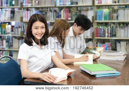 Group of Asian students in uniform studying together in library at university. University students.