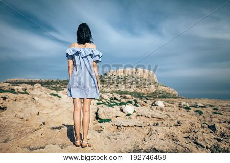 Back view of lonely woman standing on rocky desert with dramatic sky