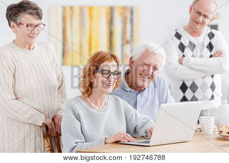 Group of smiling aged people watching old photos on laptop