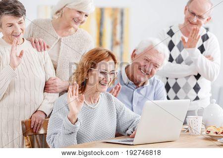 Elderly happy people talking online using laptop with old friend