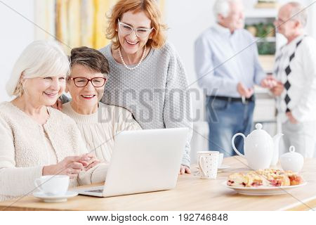 Senior woman teaching her friends how to use laptop