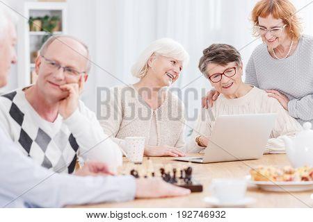 Two older men playing chess and three senior women using laptop
